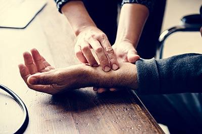 Zespół cieśni nadgarstka objawia się bólem w nadgarstku i drętwieniem dłoni. Lekarz sprawdza objawy bólu na nadgarstku poprzez jego ucisk.